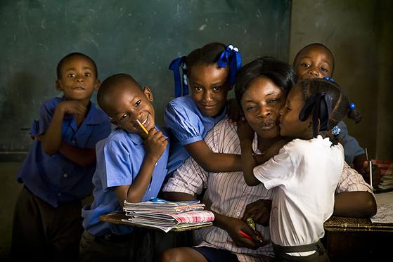 아이티에서 만난 선생님과 아이들. 고슴도치처럼 낯을 가리는 빈민가 아이들이 선생님에게 거리낌 없이 다가가 입을 맞추는 광경은 그 이전에 얼마나 많은 이야기가 쌓여 있는지 충분히 알게 했다. 이 역시 사랑이 어떤 질량과 함량을 가진 무엇처럼, 사람과 사람 사이를 오고 가고 있는 장면이었다. [사진 허호]