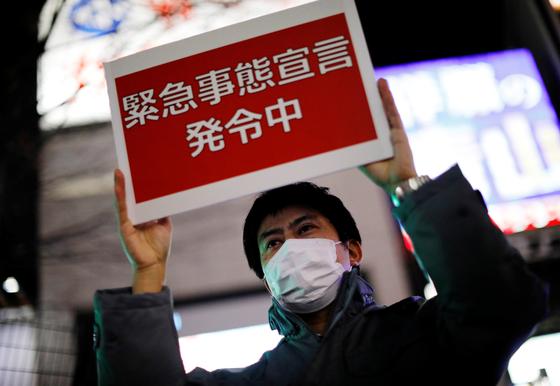 8일 일본 도쿄 지하철 직원이 '긴급사태 선언 발령 중'이라고 적힌 안내판을 들고 시민들에게 뻘리 귀가할 것을 권하고 있다. [로이터=연합뉴스]
