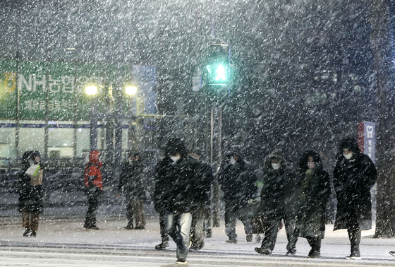 서울 등 수도권 지역으로도 3~10cm의 많은 눈이 예보된 6일 오후 퇴근길 시민들이 서울 중구 시청 앞 횡단보도를 건너고 있다. 김성룡 기자
