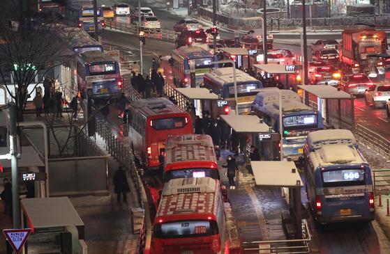 많은 눈이 내린 12일 오후 서울 중구 서울역환승센터에서 시민들이 버스를 기다리고 있다. 연합뉴스