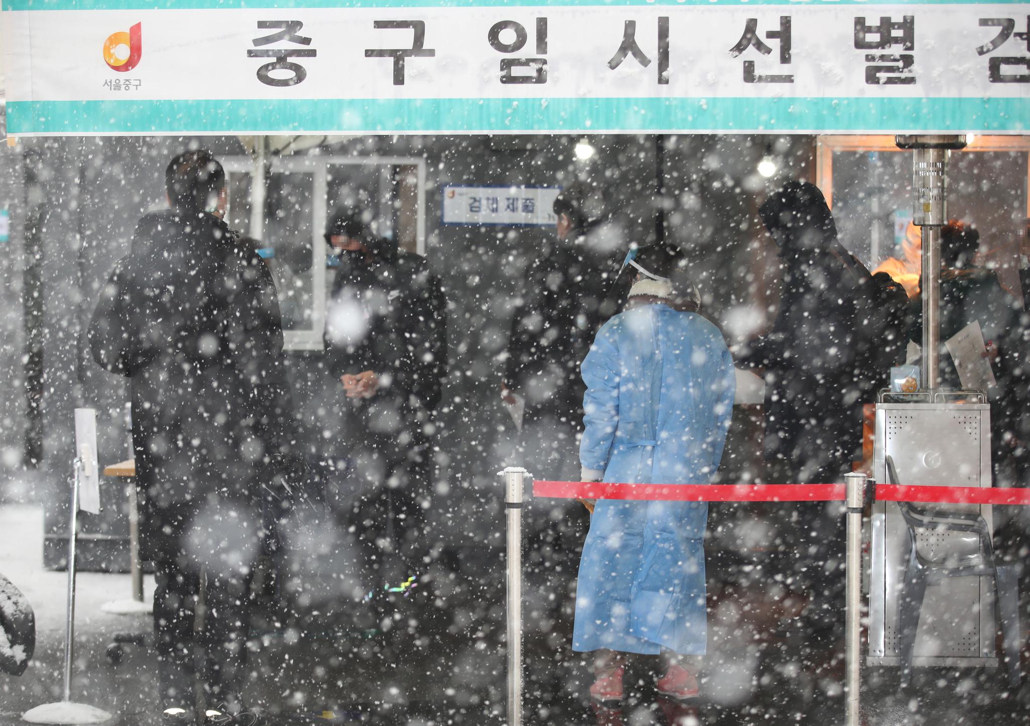 눈이 내린 12일 오후 서울역 광장에 마련된 코로나19 임시 선별검사소에서 시민들이 검사를 받고 있다. 연합뉴스
