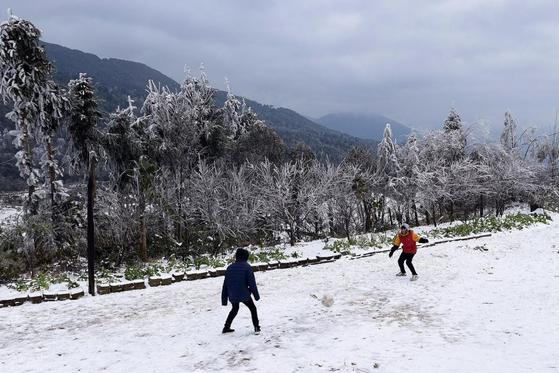 지난 11일 라오까이성에서 주민들이 눈 내린 길을 걷고 있다. 로이터=연합뉴스