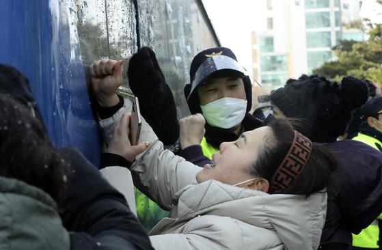 입양 뒤 양모의 학대로 숨진 '정인이 사건' 첫 공판이 13일 서울 양천구 남부지법에서 열렸다. 이날 분노한 시민들이 정인이 양모를 태운 호송버스에 눈덩이를 던지고, 차량을 손으로 치고 있다. 김성룡 기자