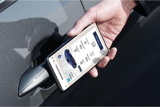 현대 '디지털 키'를 통해 최신 아반떼의 차량 문을 여는 모습. 특정 스마트폰에 대한 홍보를 방지하기 위해 스마트폰 앞면 카메라 부분은 포토샵으로 처리했다. [사진 현대차]