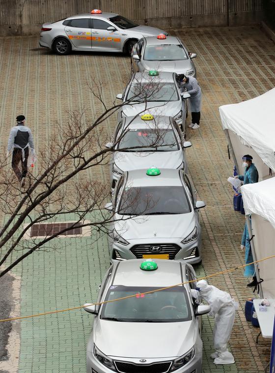 지난 11일 부산지역 택시 기사들이 연제구 아시아드주경기장 주차장에 마련된 이동 선별검사소에서 드라이브스루 방식으로 코로나19 진단검사를 받고 있다. 송봉근 기자