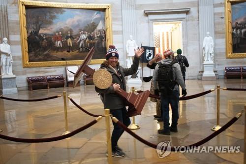 낸시 펠로시 의장 연설대 가져가는 등 의회 난입 혐의로 체포된 애덤 존슨. [AFP=연합뉴스]