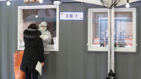 신종 코로나바이러스감염증(코로나19) 신규 확진자가 562명을 기록하면서 이틀 연속 500명대를 유지한 13일 서울역 광장에 마련된 임시선별진료소에서 의료진이 검체 채취를 하고 있다. 뉴스1