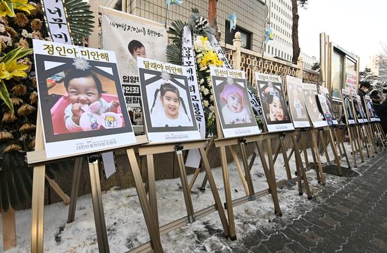 16개월 된 입양 딸 정인이를 학대해 숨지게 한 양부모에 대한 첫 공판이 열린 13일 서울남부 지방법원 앞에 학대로 숨진 아이들의 사진이 걸려 있다. 김성룡 기자