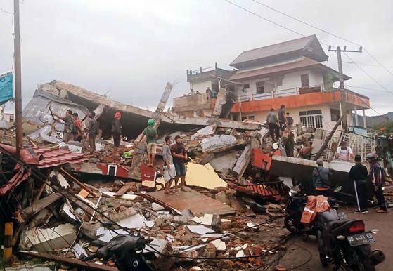 15일(현지시간) 새벽 인도네시인도네시아 술라웨시 서부 마무주 지역에서 진도 6.2의 강진이 발생해 사상자가 속출했다. 이날 주민들이 무너진 건물에서 수색작업을 벌이고 있다. [AP=연합뉴스]