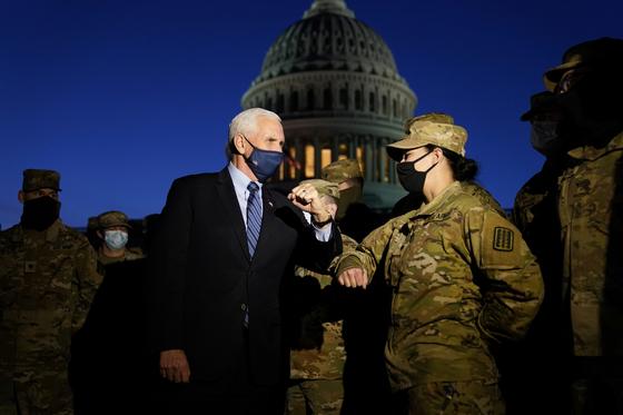 14일(현지시간) 마이크 펜스 미 부통령이 워싱턴 의사당 주변을 지키고 있는 주 방위군 대원과 팔꿈치 인사를 나누고 있다. [로이터=연합뉴스]