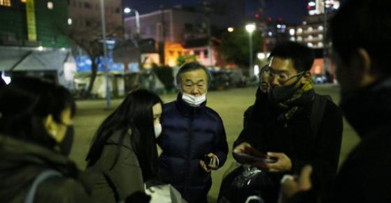 일본 오사카에서 21년째 겨울만 되면 노숙자들에게 침낭을 나눠주는 봉사를 하는 이시구로(가운데). [마이니치 신문 트위터]