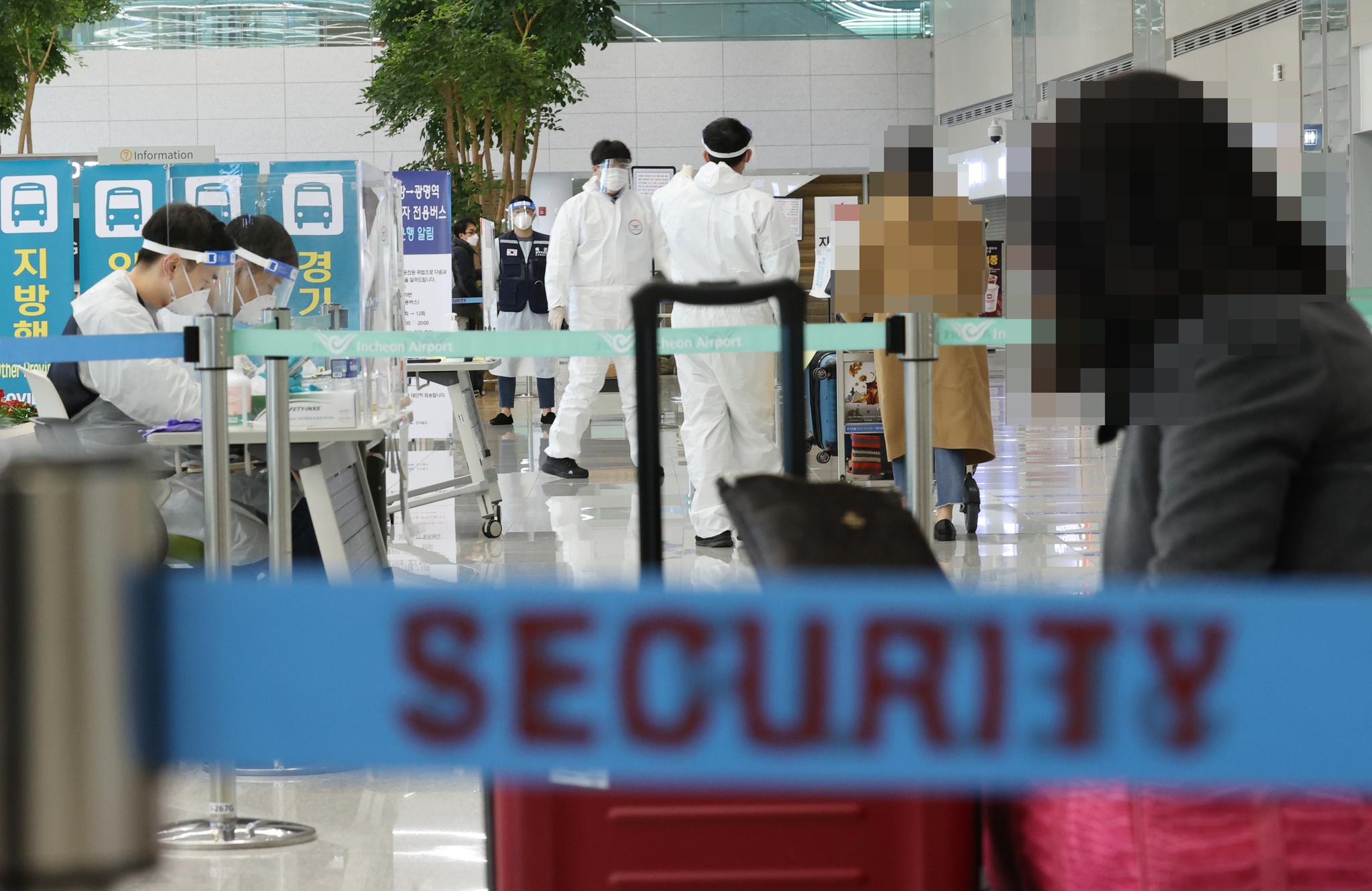 지난해 12월 30일 오후 인천국제공항 제2여객터미널 입국장에서 항공편 해외입국자들이 방역 관계자들의 안내를 받고 있다. 연합뉴스