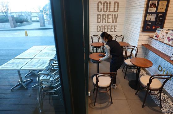 17일 서울 시내 한 카페에서 종업원이 내부 테이블을 닦고 있다. 18일부터 정부의 새로운 방역조치에 따라 그동안 포장·배달만 허용됐던 카페에서 오후 9시까지 매장에서 취식할 수 있게 된다. 연합뉴스
