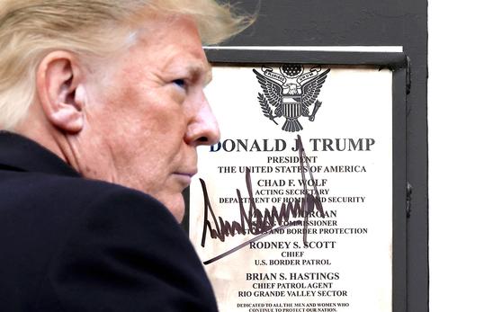 도널드 트럼프 미국 대통령이 12일(현지시간) 텍사스주 알라모의 미국·멕시코 국경장벽을 시찰하던 중 장벽에 부착된 명판에 서명을 하고 있다. [AFP=연합뉴스]