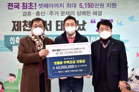 이상천 제천시장(왼쪽)이 18일 제천시 화산동 행정복지센터에서 올해 셋째를 출산한 주민 박모(36·가운데)씨를 초대해 주택자금 지원 행사를 열었다. [사진 제천시]