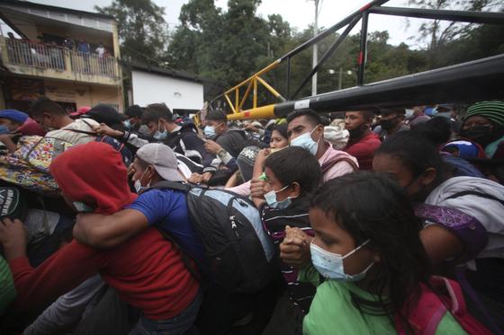 미국으로 가기를 희망하는 온두라스 이민자들이 과테말라 국경에서 군인들을 밀어내며 과테말라로 들어서고 있다. [AP=연합뉴스]