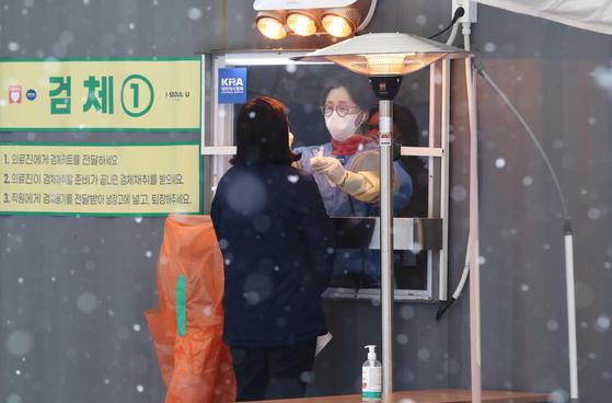 18일 오전 서울광장에 마련된 코로나19 임시 선별검사소에서 의료진이 검체 채취를 하고 있다. 연합뉴스