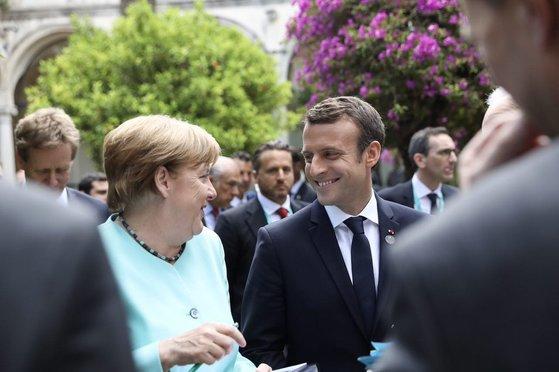 2017s년 5월 26일 이탈리아 시칠리아에서 개최된 주요 7개국(G7) 정상회담에서 앙겔라 메르켈 독일 총리(왼쪽)가 에마뉘엘 마크롱 프랑스 대통령과 환담을 나누고 있다. 다른 정상들의 화기애애한 분위기와 달리 이날 트럼프는 혼자 골프 카트를 타고 별도로 이동했다. 사진=마크롱 대통령 트위터
