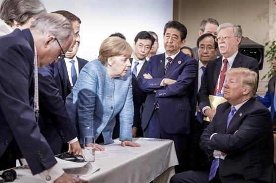 2018년 6월 9일 캐나다에서 열린 G7 정상회의에서 보호무역 배격 입장이 담긴 공동성명을 거부하고 버티는 도널드 트럼프(오른쪽). 다른 나라 정상들이 설득하고 있지만 요지부동이다. AP=연합뉴스