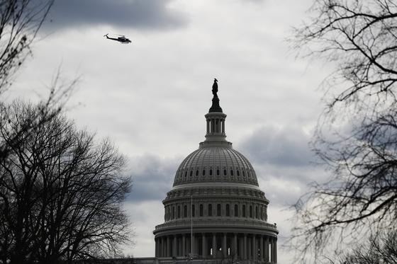 지난 18일 미국 워싱턴 연방의사당 위로 경찰 헬기가 날고 있다. 연방의회는 미국의 패권국가로 성장하는 동안 전비와 국제원조 자금을 풍부하게 제공했다. AP=연합뉴스