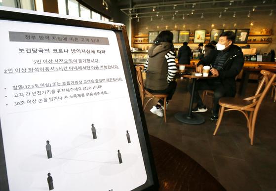 포장·배달만 가능했던 카페에서 매장 내 취식이 가능해진 18일 대전시내 카페를 찾은 시민들이 테이블에 앉아 커피를 마시고 있다. 2인 이상 좌석 이용시 1시간 이내에서만 가능하다는 안내문이 놓여있다. 뉴스1