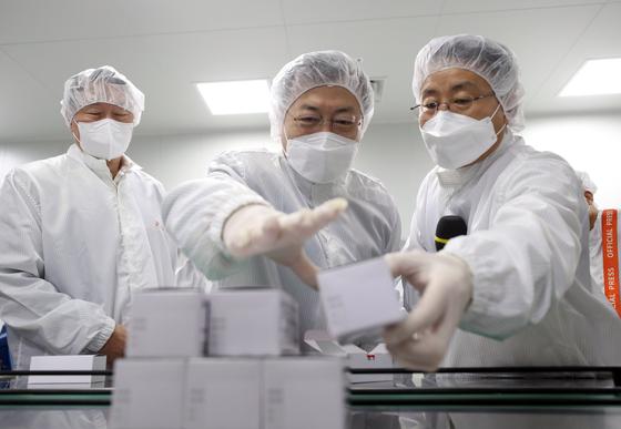 문재인 대통령이 20일 SK바이오사이언스 공장에서 백신을 살펴보고 있다. 왼쪽은 최태원 SK 회장. 연합뉴스