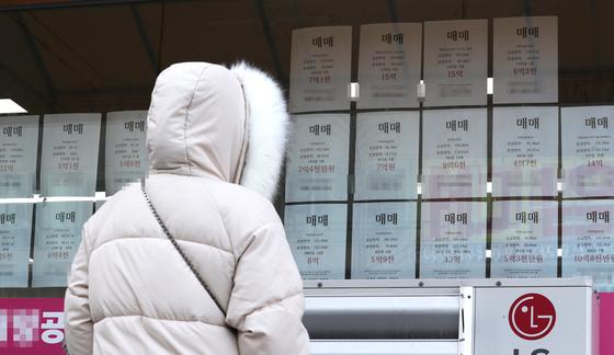 세종시의 한 공인중개사 사무소 유리창에 붙은 아파트 매매가격표를 한 시민이 바라보고 있다. [연합뉴스]