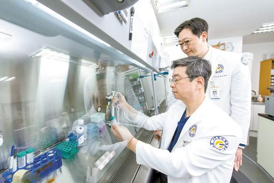 연세사랑병원 고용곤 병원장(왼쪽)이 세포치료연구소에서 김용상 원장(오른쪽)과 무릎 연골을 되살려주는 줄기세포 연구를 하고 있다. 김동하 객원기자
