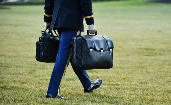 1월 20일(현지시간) 도널드 트럼프 미국 대통령과 영부인 멜라니아 여사가 백악관을 떠나기 전, 군 관계자가 미국 대통령의 핵가방을 대통령 전용기에 운반하고 있다. AFP=연합뉴스