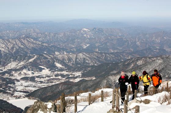 겨울 산행은 여느 계절보다 복장이 중요하다. 산의 지형과 높이에 따라 기상 상황이 수시로 바뀌는 탓에 보온, 방한 의류와 등산용품을 잘 갖춰야 한다. 사진은 덕유산 능선을 걷는 사람들. [중앙포토]