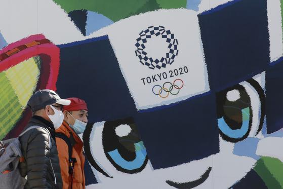 일본 도쿄 시민이 시내의 도쿄 올림픽 포스터 앞을 지나가고 있다. 6개월 앞으로 다가온 도쿄 올림픽은 코로나19 여파로 취소 또는 연기 가능성이 나오고 있다. [AP=연합뉴스]