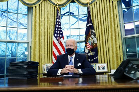 조 바이든 대통령이 20일 백악관 집무실 책상에 앉아 있다.[로이터=연합뉴스]
