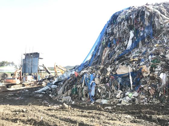 Gyeongbuk Uiseong-gun Danmil-myeon Garbagesan in the past.  Heavy equipment moves between the piles of garbage. [중앙포토]