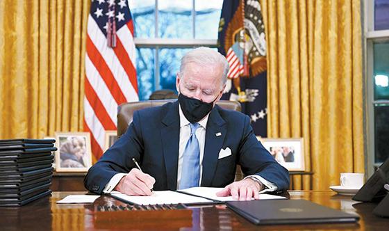미국의 조 바이든 대통령이 취임 당일인 지난 20일(현지시간) 오후 백악관 집무실에서 마스크를 쓰고 업무를 보고 있다. AFP=연합뉴스
