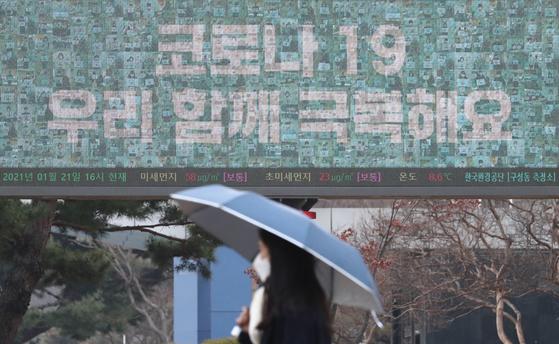 전국적으로 흐리고 비가내린 21일 오후 대전 유성구 한국과학기술원(KAIST) 캠퍼스에서 우산을 쓰고 지나는 학생 뒤로 보이는 전광판에 '코로나19 우리 함께 극복해요' 문구가 적혀 있다. *사진 속 인물과 기사내용은 관련 없습니다. 뉴스1