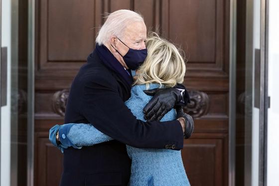 바이든 대통령 부부가 20일(현지시간) 백악관 노스포티코 현관앞에 도착해 포옹을 하고 있다. [AP=연합뉴스]