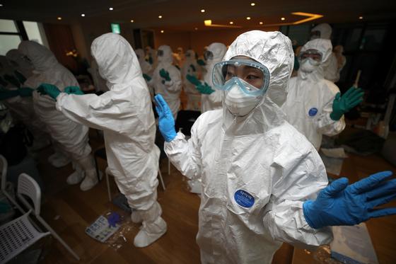 18일 오전 서울시가 시내 첫 감염병 전담 요양병원으로 지정한 강남구 '느루요양병원'에서 열린 오리엔테이션에 참가한 근무자들이 방호복과 보호장구를 착용해보고 있다. [연합뉴스]