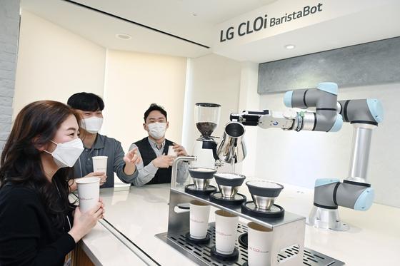 서울 영등포구 LG트윈타워에 설치된 'LG 클로이 바리스타봇'을 이용하는 임직원들. LG전자 제공