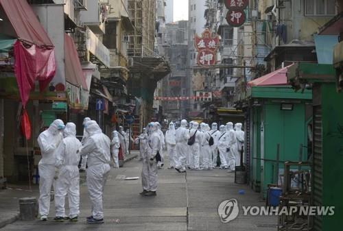 23일 전격 봉쇄된 홍콩 도심의 건물들 앞의 방역 요원들 [AP=연합뉴스]