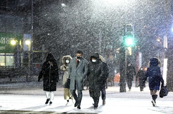 서울 등 수도권 지역으로도 3에서 10cm의 많은 눈이 예보된 6일 오후 퇴근길 시민들이 서울 중구 시청 앞 횡단보도를 건너고 있다. 김성룡 기자