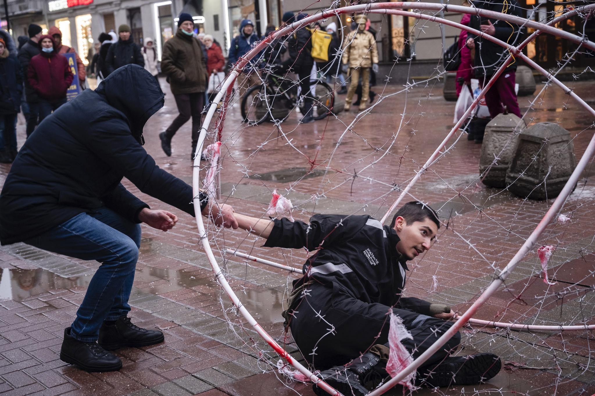 사복 차림의 러시아 경찰이 24일 모스크바에서 야권운동가 나발니의 석방을 요구하는 시위를 벌이던 파벨 크리세비치를 체포하고 있다. 크리세비치는 철조망 속에 자신을 가두는 퍼포먼스를 벌이던 도중 체포됐다. [AP=연합뉴스]