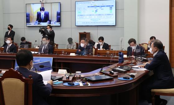 문재인 대통령이 25일 오후 청와대에서 열린 복지부·식약처·질병청 2021년 업무보고에 참석, 김강립 식품의약품안전처장 보고를 받고 있다. 연합뉴스