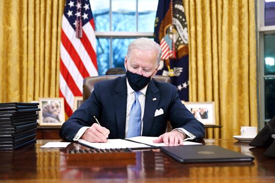 20일(현지시간) 백악관 집무실에서 마스크를 쓰고 업무를 보고있는 조 바이든 미국 대통령 [AFP]