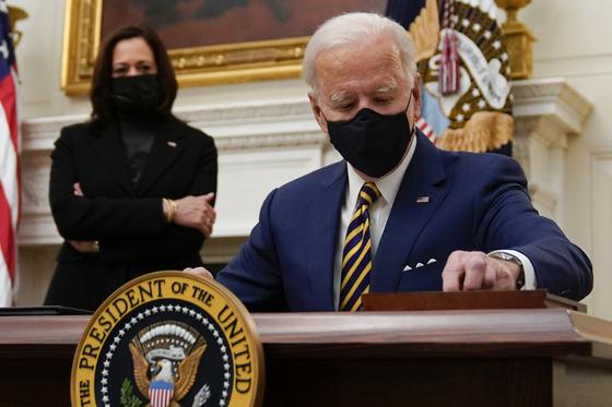 조 바이든 미국 대통령(오른쪽)이 지난 22일 카멀라 해리스 부통령이 지켜보는 가운데 코로나19 대응책 행정명령에 서명하고 있다. [AP=연합뉴스]