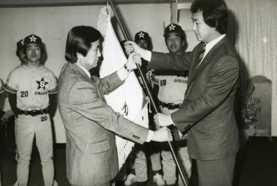 삼미슈퍼스타즈의 김현철 사장(오른쪽)이 이혁근 단장에게 단기를 수여하고 있다.