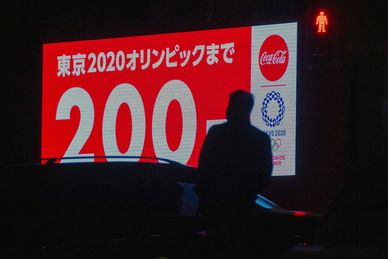4일 일본 도쿄의 한 시민이 도쿄올림픽 D-200을 알리는 대형 스크린 옆을 지나고 있다. 일본 정부는 도쿄올림픽 강행을 외치지만, 안팎의 시선은 싸늘하다. AP=연합뉴스