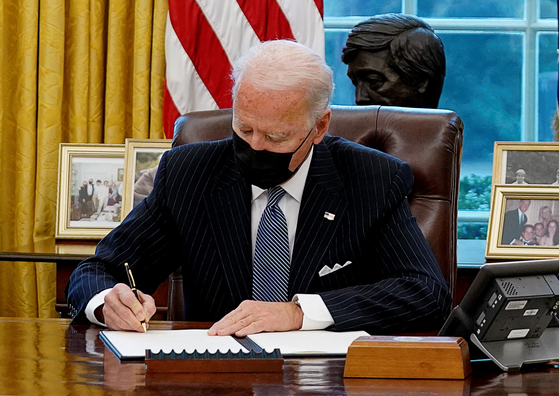 조 바이든 미국 대통령이 25일(현지시간) 백악관 집무실에서 트럼프 행정부의 성소수자 군복무 규정을 뒤집는 행정명령에 서명하고 있다. 바이든 대통령은 이날 연방 정부의 미국산 제품 우선 구매법(Buy American Act) 행정명령에도 서명했다. [로이터=연합뉴스]