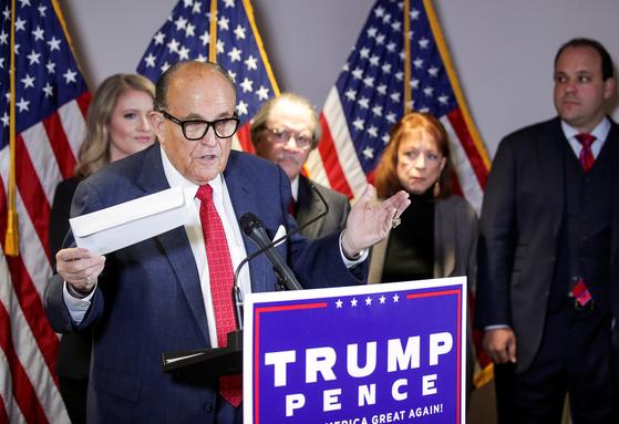 트럼프 대통령 변호인인 루디 줄리아니 전 뉴욕시장이 우편투표 용지를 들어 보이며 조작 의혹을 제기하고 있다. [로이터]
