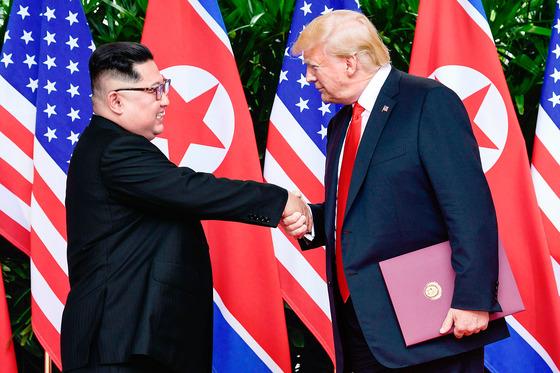 2018년 6월 12일 싱가포르에서 개최된 1차 북미 정상회담에서 김정은(왼쪽) 북한 국무위원장과 도널드 트럼프 미국 대통령이 악수를 나누는 모습. [연합뉴스]