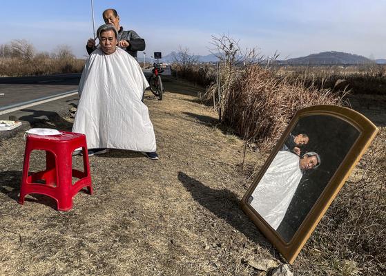 경기도 김포시 고촌읍 한강 아라자전거길에서 25일 거리의 이발사 A씨(71)가 단골손님인 김은기 씨(73)의 머리를 깎아주고 있다. 이발비는 무료다. 김성룡 기자